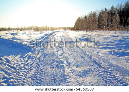 rural road through winter field - stock photo