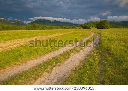Rural road to the mountains and the storm sky - stock photo