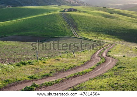 rural road to the old farm on the green hills at the twilight - stock photo