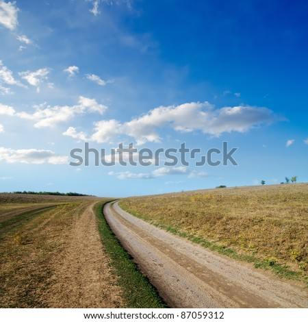 rural road under cloudy sky - stock photo
