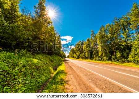 Rural road up the hill under the rays of the sun. View from the side of the road - stock photo