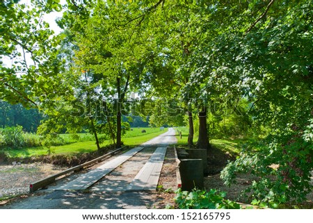 Rural road with a small bridge over dried creek on a sunny summer day. - stock photo