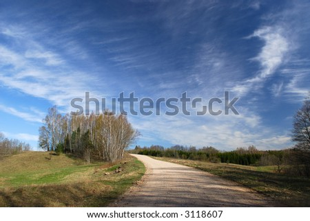 Rural road with the blue sky in the spring - stock photo