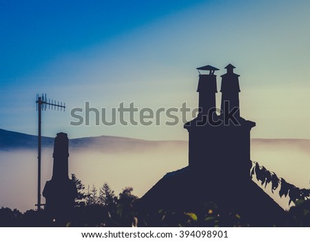 Rural Rooftop And Chimney Against Misty Dusk With Copy Space - stock photo