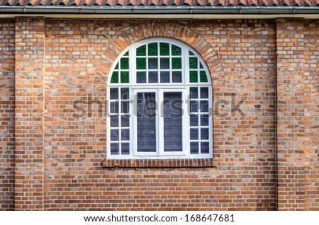 rural round arch window in a brick wall building, lower saxony, germany - stock photo