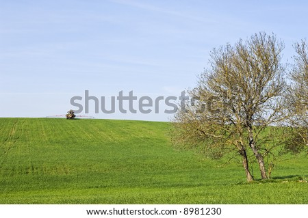 Rural scene - green field harvest landscape in spring with tractor