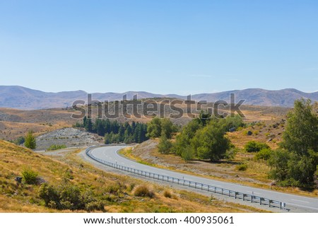 Rural Scene of Asphalt Road with Meadow and Mountain Range, South Island, New Zealand