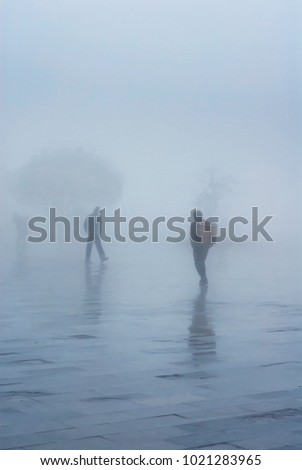Rural Scene of people walk through the square during cold dense foggy day in season change.