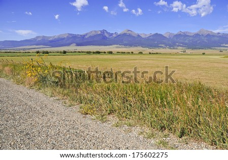 Rural Scene with Farm land and Rocky Mountains as Background - stock photo