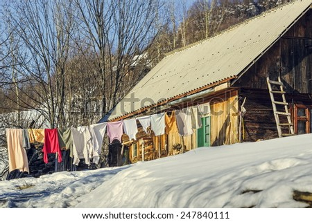 Rural scene with laundry drying on a clothesline outside in the cortyard on a winter sunny day. - stock photo