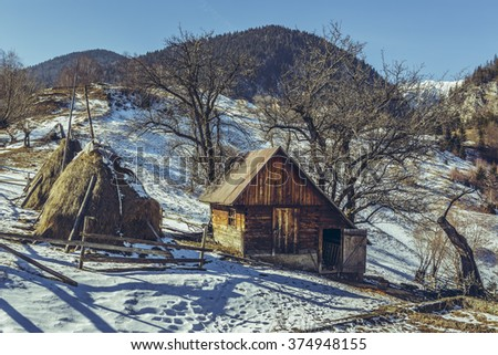 Rural scene with traditional Romanian wooden stable and haystacks, on a sunny spring day with melting snow, uphill in Magura village, Brasov county, Transylvania region, Romania. - stock photo
