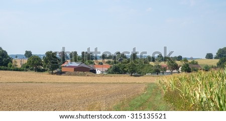 rural scenery including a small village in sunny ambiance at summer time - stock photo
