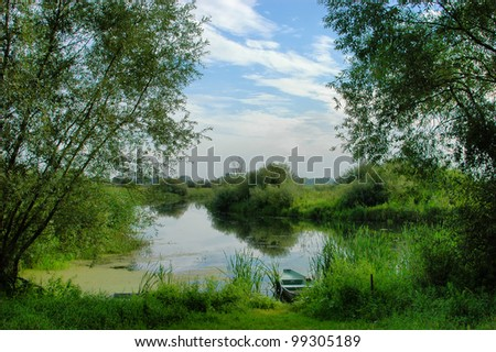 rural scenery with river and boat in Central Europe - stock photo