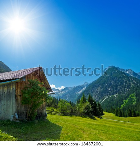 rural scenery with wooden hut in the mountains - stock photo