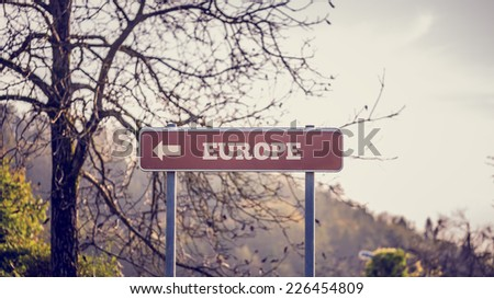 Rural signpost bearing the word - Europe - with an arrow pointing to the left of the frame indicating - this way. - stock photo