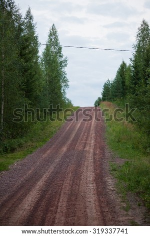 Rural small uphill gravel road in finland - stock photo
