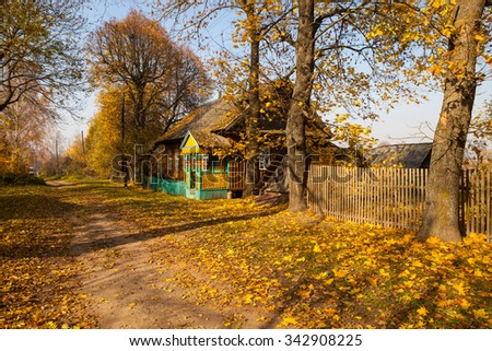 Rural street in village with wooden house, trees and golden foliage in autumn on sunny day