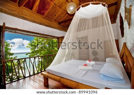 Rural style bedroom with canopy bed with sea view - stock photo