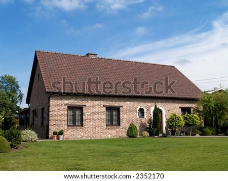 Rural suburban house  with garden in belgium. Summer period, sunny day. Real estate concept. - stock photo