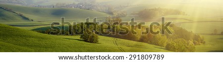 Rural sunny landscape with fields, waves and wooden hunting shack  - panoramic view - stock photo