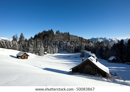 Rural sunny winter landscape with occupied chalets - stock photo