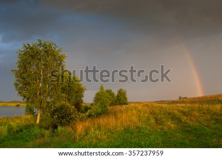 Rural sunset landscape with trees, rainbow and dark clouds - stock photo