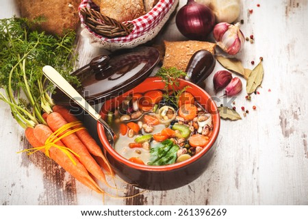 Rural vegetarian broth soup with colorful vegetables and rustic clay pot. - stock photo
