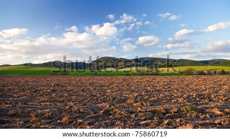 Rural view with plowed field in hills - stock photo