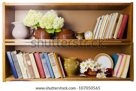Rural village bookshelf with old broken  books, ceramic pots, clocks and daisies flowers. Isolated. Front view - stock photo