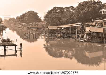 Rural villages along the canal side, Pratumtani Province  handlers style sepia photos . - stock photo