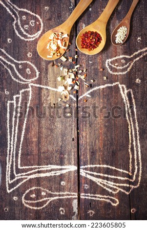 Rural vintage wood kitchen table with drawing blank cook book with spices for cooking/ cooking idea concept - stock photo