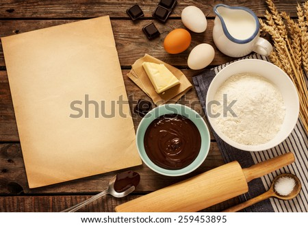 Rural vintage wooden kitchen table with old blank sheet of paper and baking cake ingredients (chocolate, eggs, flour, milk, butter, sugar). Background layout with free recipe text space. - stock photo