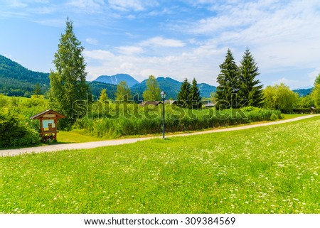 Rural walking path along green meadow with traditional countryside house in background, Weissensee lake, Alps Mountains, Austria - stock photo