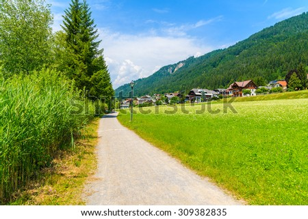 Rural walking path along green meadow with traditional countryside houses in background, Weissensee lake, Alps Mountains, Austria - stock photo