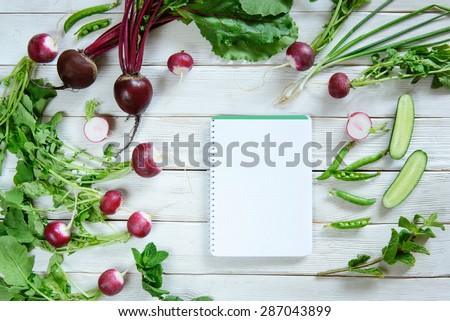Rural white wood kitchen table with blank cook book for shopping list with salad ingredients (beets, radishes, peas, cucumber, parsley, mint). Blanck recipe book, copy space - stock photo