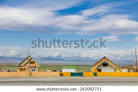 Rural wooden countryside houses surrounded by beautiful Altai mountain landscape during summer - stock photo