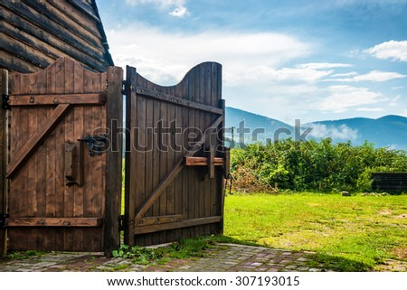 Rural wooden gate and green lawn with grass, mountains, blue sky - stock photo
