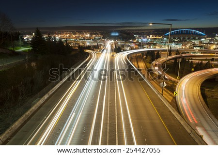 Rush Hour, Seattle. Interstate freeways converge on the Seattle landscape with Elliott Bay and the waterfront in the background during a dramatic sunset. - stock photo