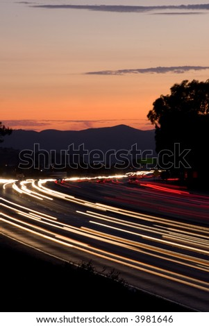 Rush hour traffic at twilight on a busy and fast moving freeway or highway - stock photo