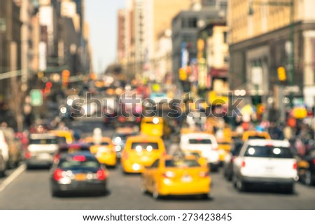 Rush hour with defocused cars and yellow taxi cabs - Traffic jam in Manhattan downtown - Blurred bokeh postcard of New York City with warm sunny day color tones - Real life transportation concept - stock photo