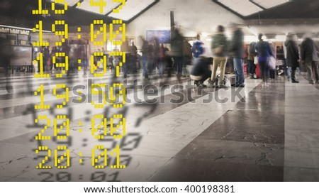 Rush hour with people in blurred motion at a railway station, with departure times i yellow in foreground - stock photo