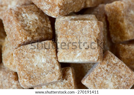 Rushy raw sugar cubes close up - stock photo