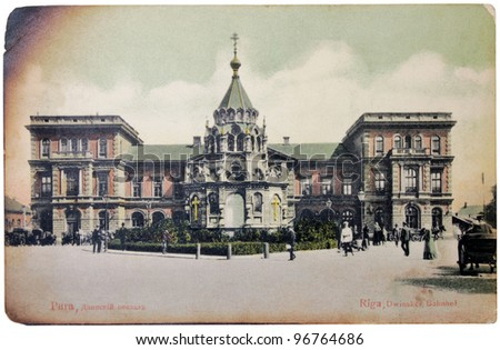 RUSSIA - CIRCA 1906: a postcard printed by RUSSIA shows hand tinted photo of Dwinsky Railroad Station in Riga. Postcard is partially burned on the edges, circa 1906. - stock photo