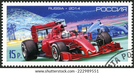 RUSSIA - CIRCA 2014: A stamp printed in RUSSIA shows car of Formula One against the Iceberg Skating Centre in the Sochi, circa 2014 - stock photo