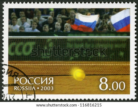 RUSSIA - CIRCA 2003: A Stamp printed in Russia shows Tennis ball and fans on tribunes, on court of a hall of Bercy - Winners of the Davis Cup 2002, circa 2003 - stock photo