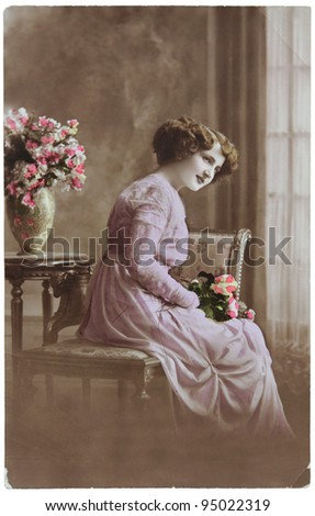 RUSSIA - CIRCA 1906: a vintage postcard printed in Russia shows hand painted photograph of young woman with flowers,  circa 1906. - stock photo
