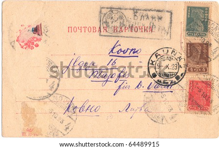 RUSSIA - CIRCA 1923: A vintage used postcard and postage stamps sent from Moscow to Kaunas (Lithuania). Rich stain and paper details. Can be used as background, series, circa 1923