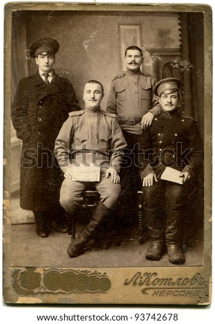 RUSSIA - CIRCA 1914 - 1917: An antique photo shows three soldiers and a student, Kherson, Russian Empire, now Ukraine, period of the First World War Russian text: Kolov (photographer), Kherson