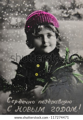 RUSSIA-CIRCA 1929: Antique postcard with a child in a winter landscape, text saying 'Happy New Year' in Russian,  circa 1929 - stock photo