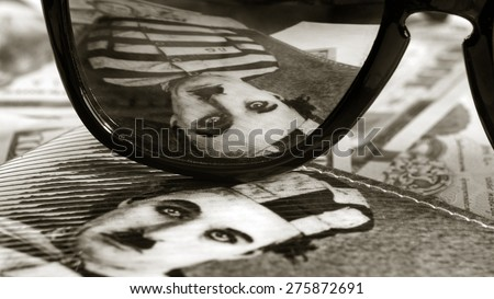 RUSSIA- CIRCA 2015:  Image scene from an film with comic actor Charlie Chaplin reflected in glasses, circa 2015.Charlie Chaplin was an English comic actor and filmmaker who rose to fame in the silent  - stock photo